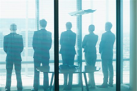 five people - Silhouette of business people in a row looking out office window Stock Photo - Premium Royalty-Free, Code: 635-06045053