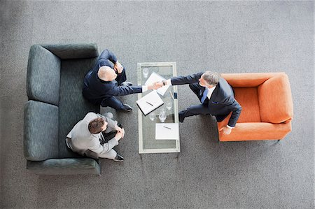 Businessmen shaking hands across coffee table in office lobby Stock Photo - Premium Royalty-Free, Code: 635-06045065