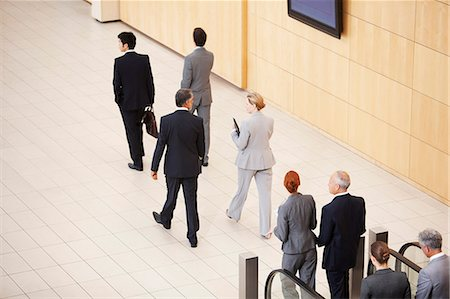 Business people stepping off escalator Stock Photo - Premium Royalty-Free, Code: 635-06045069