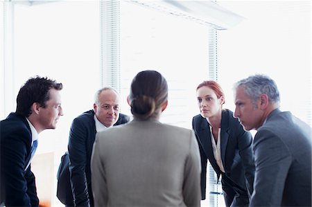 Business people leaning in circle and talking Stock Photo - Premium Royalty-Free, Code: 635-06045072