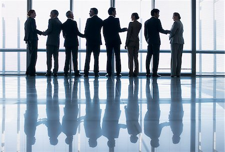 Business people shaking hands in a row at lobby window Stock Photo - Premium Royalty-Free, Code: 635-06045104