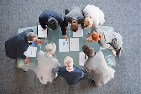 Business people huddled around paperwork on table Stock Photo - Premium Royalty-Free, Code: 635-06045106