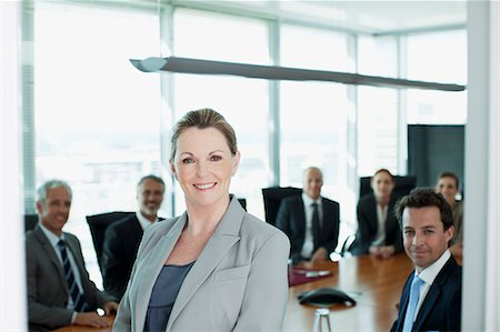 Portrait of smiling businesswoman and co-workers in conference room Stock Photo - Premium Royalty-Free, Code: 635-06045109