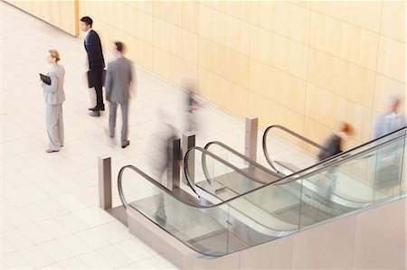 Business people standing at bottom of escalator Stock Photo - Premium Royalty-Free, Code: 635-06045126