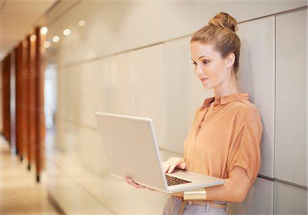 Businesswoman using laptop in corridor Stock Photo - Premium Royalty-Free, Code: 635-06045135