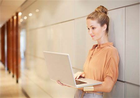 Businesswoman using laptop in corridor Stock Photo - Premium Royalty-Free, Code: 635-06045135