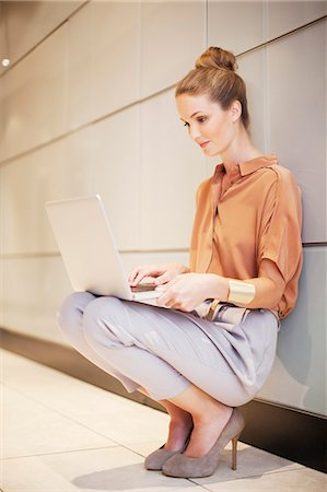 Smiling businesswoman using laptop in corridor Stock Photo - Premium Royalty-Free, Code: 635-06045147
