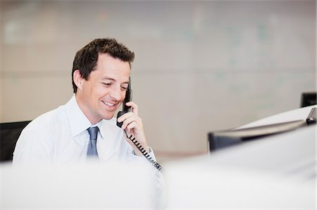 Smiling businessman talking on telephone in office Stock Photo - Premium Royalty-Free, Code: 635-06045151