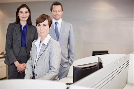 Portrait of smiling business people at desk in office Stock Photo - Premium Royalty-Free, Code: 635-06045164