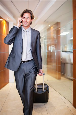 Businessman talking on cell phone and pulling suitcase Stock Photo - Premium Royalty-Free, Code: 635-06045166