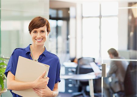 short hair - Portrait of smiling businesswoman holding binder in office Stock Photo - Premium Royalty-Free, Code: 635-06045173