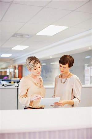 reviewing - Businesswomen reviewing paperwork in office Stock Photo - Premium Royalty-Free, Code: 635-06045204