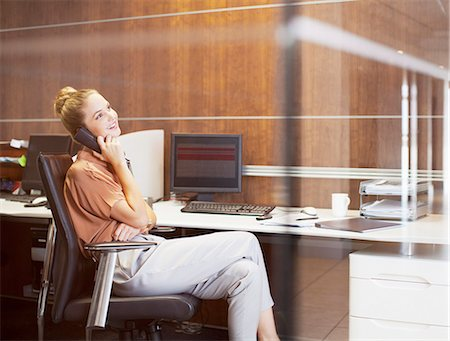 Smiling businesswoman talking on telephone in office Stock Photo - Premium Royalty-Free, Code: 635-06045206