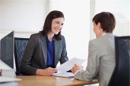 Businesswomen with paperwork talking face to face Stock Photo - Premium Royalty-Free, Code: 635-06045215