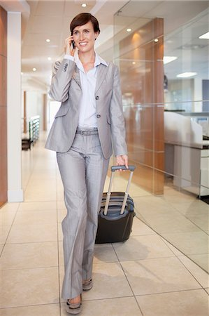 short hair - Businesswoman talking on cell phone and pulling suitcase in corridor Stock Photo - Premium Royalty-Free, Code: 635-06045219