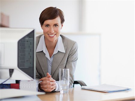 short hair - Portrait of smiling businesswoman at desk in office Stock Photo - Premium Royalty-Free, Code: 635-06045225