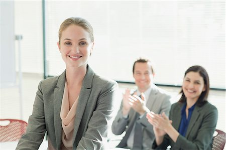 Co-workers clapping for smiling businesswoman Stock Photo - Premium Royalty-Free, Code: 635-06045227
