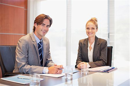 Portrait of smiling businessman and businesswoman in conference room Stock Photo - Premium Royalty-Free, Code: 635-06045220