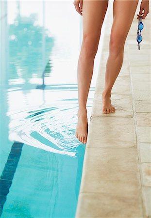 swimming pool water - Woman dipping toe in swimming pool Stock Photo - Premium Royalty-Free, Code: 635-06045249