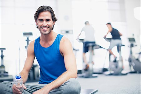 Portrait of smiling man sitting on exercise mat in gymnasium Stock Photo - Premium Royalty-Free, Code: 635-06045269