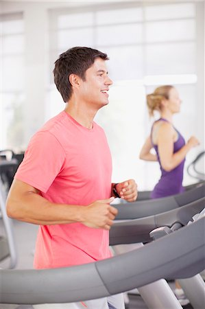Smiling man running on treadmill in gymnasium Stock Photo - Premium Royalty-Free, Code: 635-06045263