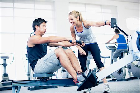 Personal trainer with man on rowing machine in gymnasium Stock Photo - Premium Royalty-Free, Code: 635-06045274