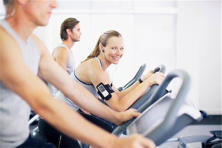 Portrait of smiling woman on exercise bike in gymnasium Stock Photo - Premium Royalty-Free, Code: 635-06045277