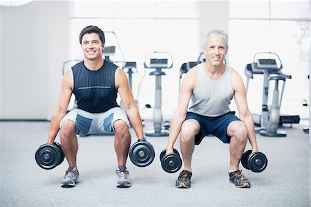 Men doing squats with dumbbells in gymnasium Stock Photo - Premium Royalty-Free, Code: 635-06045295
