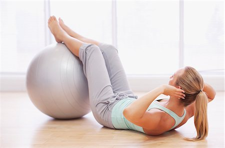 Woman doing sit-ups with fitness ball Stock Photo - Premium Royalty-Free, Code: 635-06045318