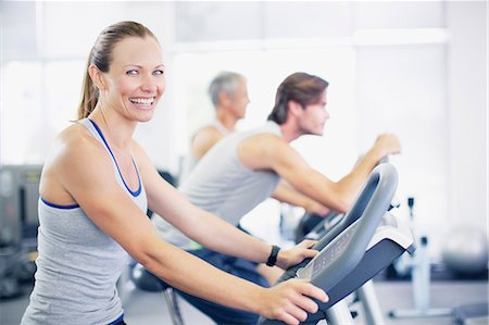 Portrait of smiling woman on exercise machine in gymnasium Stock Photo - Premium Royalty-Free, Code: 635-06045339