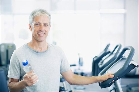 Portrait of smiling man holding water bottle on treadmill in gymnasium Stock Photo - Premium Royalty-Free, Code: 635-06045344