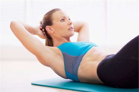 Serious woman in sports bra doing sit-ups on exercise mat Stock Photo - Premium Royalty-Free, Code: 635-06045343