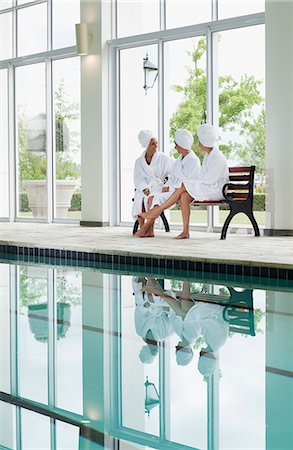 swimming pool water - Women in bathrobes talking on bench poolside at spa Stock Photo - Premium Royalty-Free, Code: 635-06045361