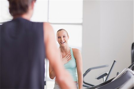 Laughing woman looking at man on treadmill in gymnasium Stock Photo - Premium Royalty-Free, Code: 635-06045362