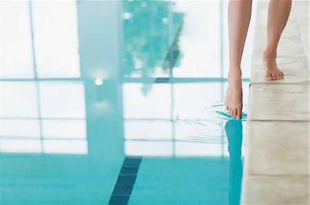 swimming pool water - Woman dipping toe in swimming pool Stock Photo - Premium Royalty-Free, Code: 635-06045373