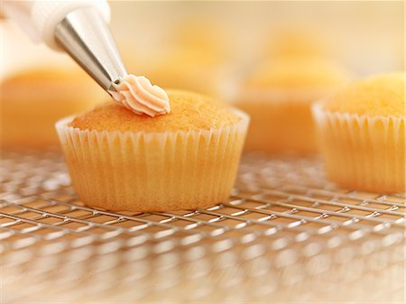 sweet   no people - Close up of cupcakes being frosted Stock Photo - Premium Royalty-Free, Code: 635-06045508