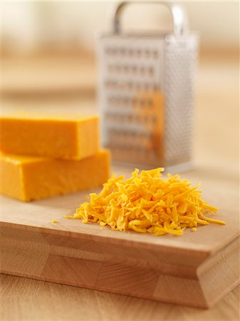 Close up of shredded cheese on cutting board Stock Photo - Premium Royalty-Free, Code: 635-06045502