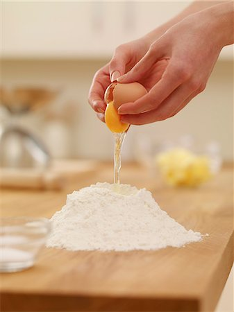Woman cracking egg over flour nest Stock Photo - Premium Royalty-Free, Code: 635-06045515