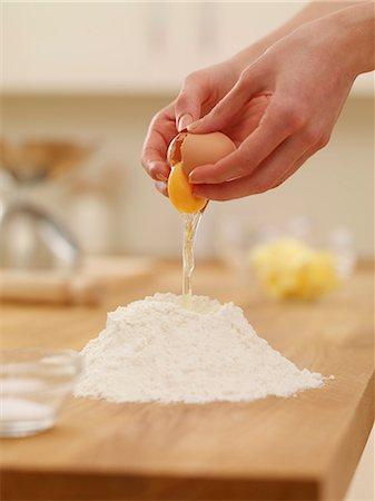 Woman cracking egg over flour nest Stock Photo - Premium Royalty-Free, Code: 635-06045515