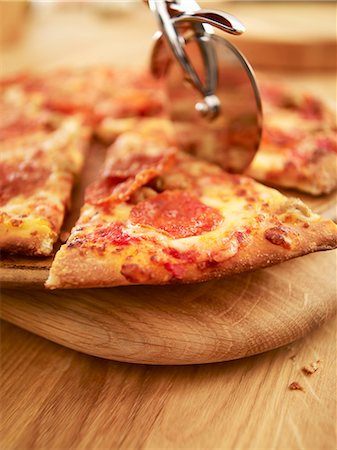 Pizza being sliced Stock Photo - Premium Royalty-Free, Code: 635-06045511
