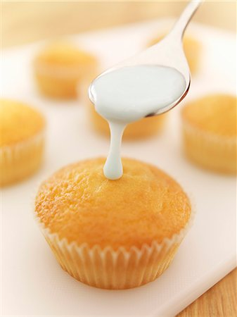 sweet   no people - Spoon of icing dripping on cupcake Stock Photo - Premium Royalty-Free, Code: 635-06045524