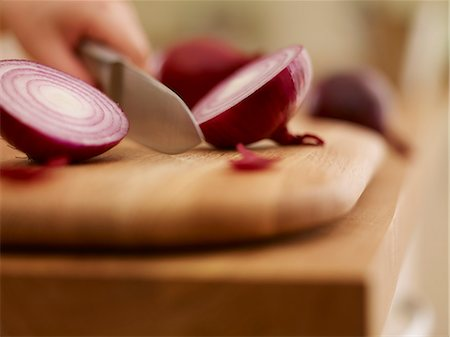 Knife chopping red onion on cutting board Stock Photo - Premium Royalty-Free, Code: 635-06045525
