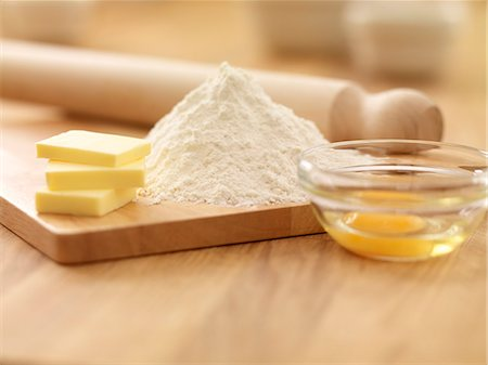 Rolling pin, flour, butter and egg on cutting board Stock Photo - Premium Royalty-Free, Code: 635-06045526