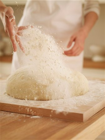 Woman dusting dough with flour Stock Photo - Premium Royalty-Free, Code: 635-06045557