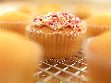 self indulgence - Close up of sprinkled cupcake cooling on wire rack Stock Photo - Premium Royalty-Free, Code: 635-06045563