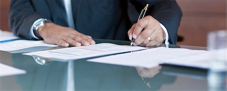 Businessman signing contract at table Stock Photo - Premium Royalty-Free, Code: 635-06045580