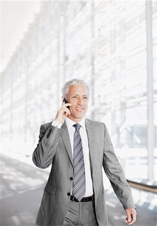 Smiling businessman talking on cell phone in corridor Stock Photo - Premium Royalty-Free, Code: 635-06045582