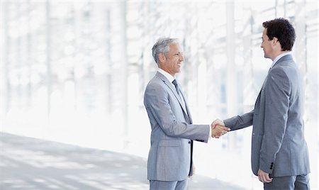 Smiling businessmen shaking hands in modern corridor Stock Photo - Premium Royalty-Free, Code: 635-06045590