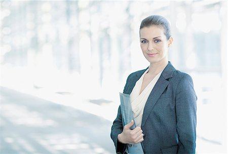 Portrait of smiling woman standing in corridor Stock Photo - Premium Royalty-Free, Code: 635-06045591