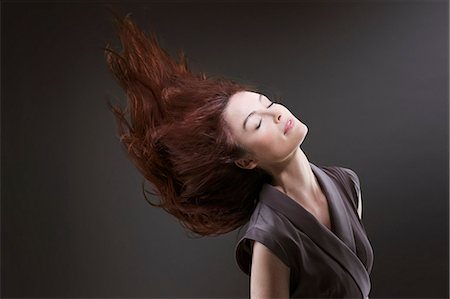 Woman with eyes closed flipping hair Stock Photo - Premium Royalty-Free, Code: 635-06045625